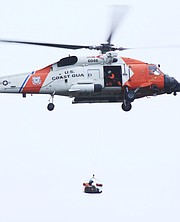 A U.S. Coast Guard chopper carries a rescuer headed toward people trapped on v roofs on San Leandro Lane.