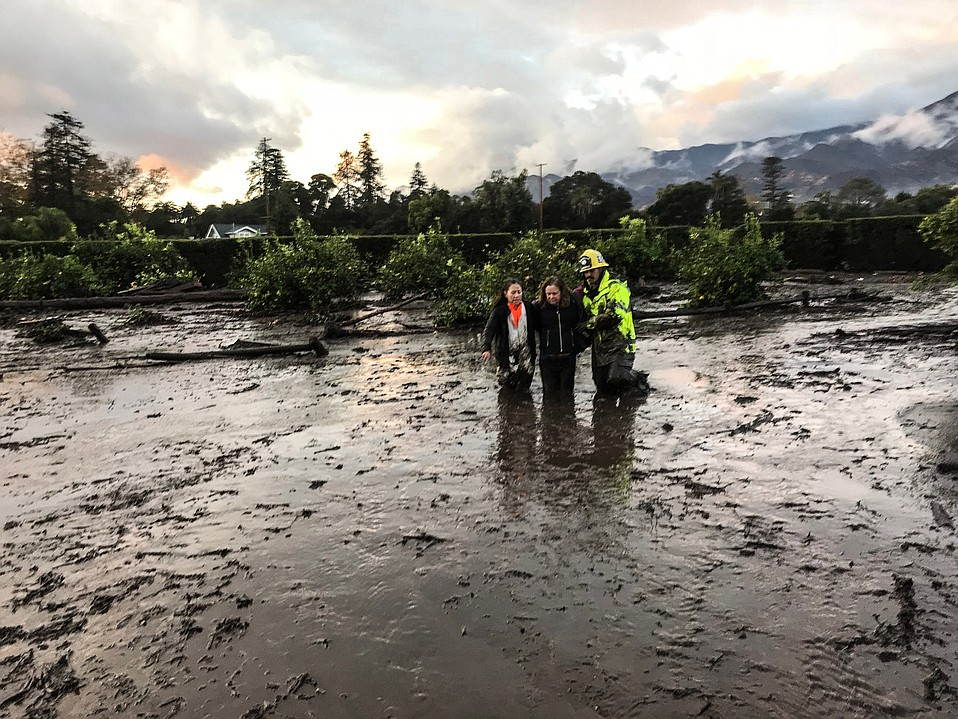 A firefighter helps two Montecito residents pick their way to Jameson Lane.