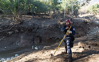 A captain with the Compton Fire Department stands at the newly formed eastern bank of Cold Spring Creek, some 30 feet from the creek bed below. Multiple crews spent Thursday scouring the waterways near East Mountain Road, searching for survivors.