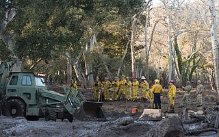 Firefighters are joined by members of the Army Corps of Engineers to assess a home that suffered substantial damage when Montecito Creek veered to the west before crossing over East Mountain Drive, cutting a new path near Sycamore Canyon Road.