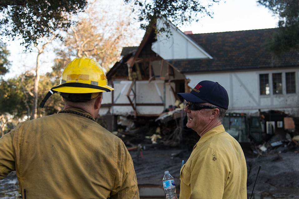 Firefighters from Kern County assess a home near Sycamore Canyon Road. The crew had been working on the site for two days after a body was recovered in the home. The instability of the wreckage demanded precision in entering and searching what remained.