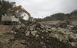 Heavy machinery works to break down and truck out boulders from the Cold Spring Creek debris basin. (Jan. 19, 2018)