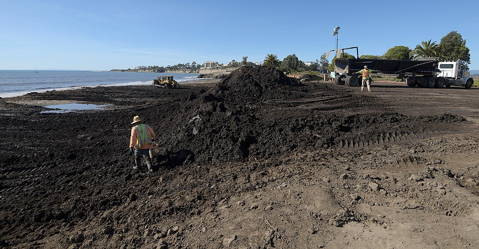 County workers conduct a final check of dirt dumped at Goleta Beach.