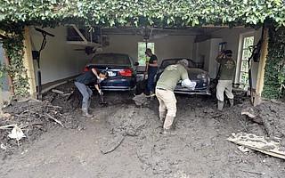 Volunteer crews help dig out cars still stuck in mud on Santo Tomas Lane.