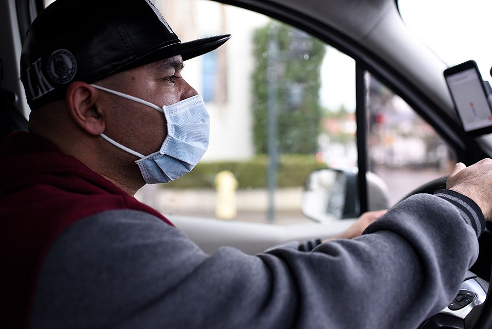 Uber driver Eddie Reyes wears a mask to protect himself from the flu. He offers masks to his passengers as well.