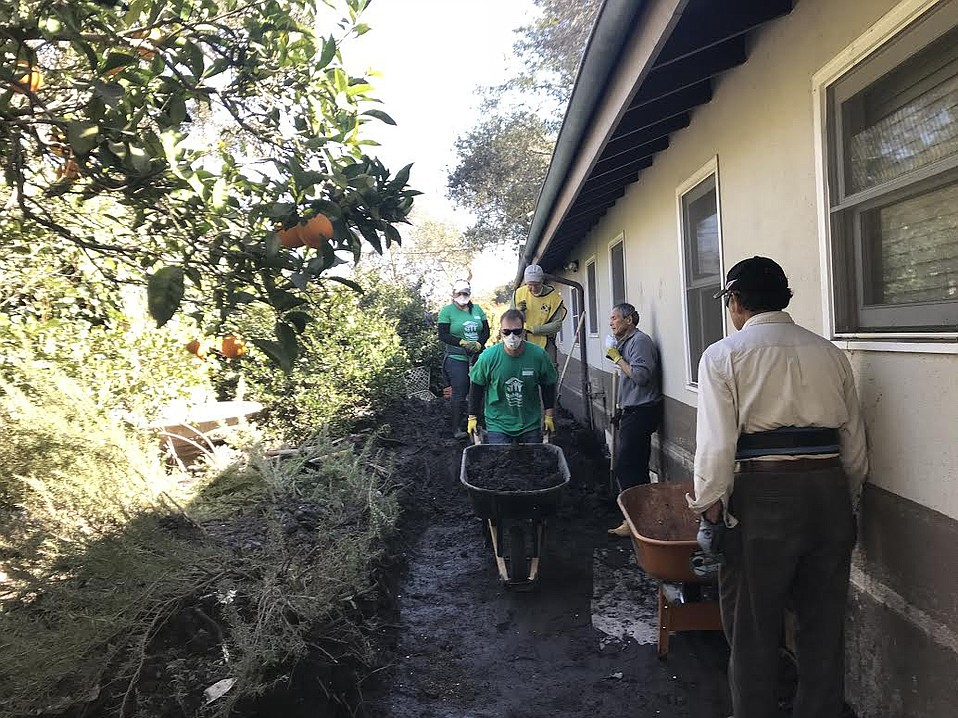Habitat for Humanity volunteers clear mud from the exterior walls of a Montecito home.