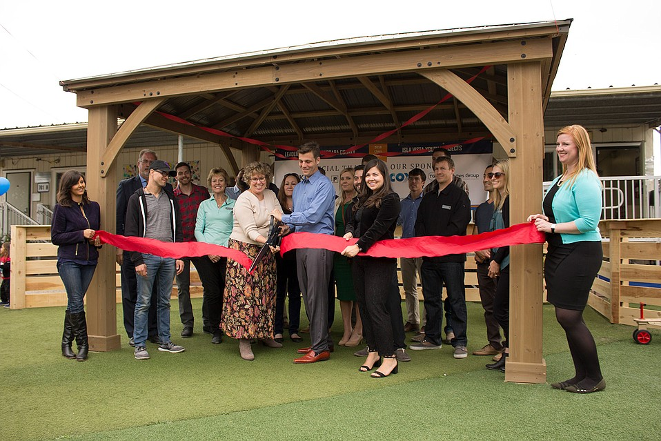 A cohort from Leadership Santa Barbara and Lori Goodman, executive director of the Isla Vista Youth Projects (pictured center-left), cut the ribbon in front of a new gazebo at the Isla Vista Youth Projects Children's Center.