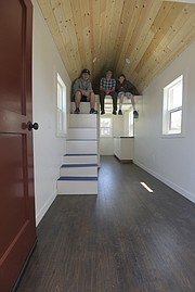 "Dos Pueblos students (from left) Finn McKenna, Maclane ""Mac"" Diehl, and  Zack Tedeschi sit inside the tiny home that their class has been working on for more than two years."