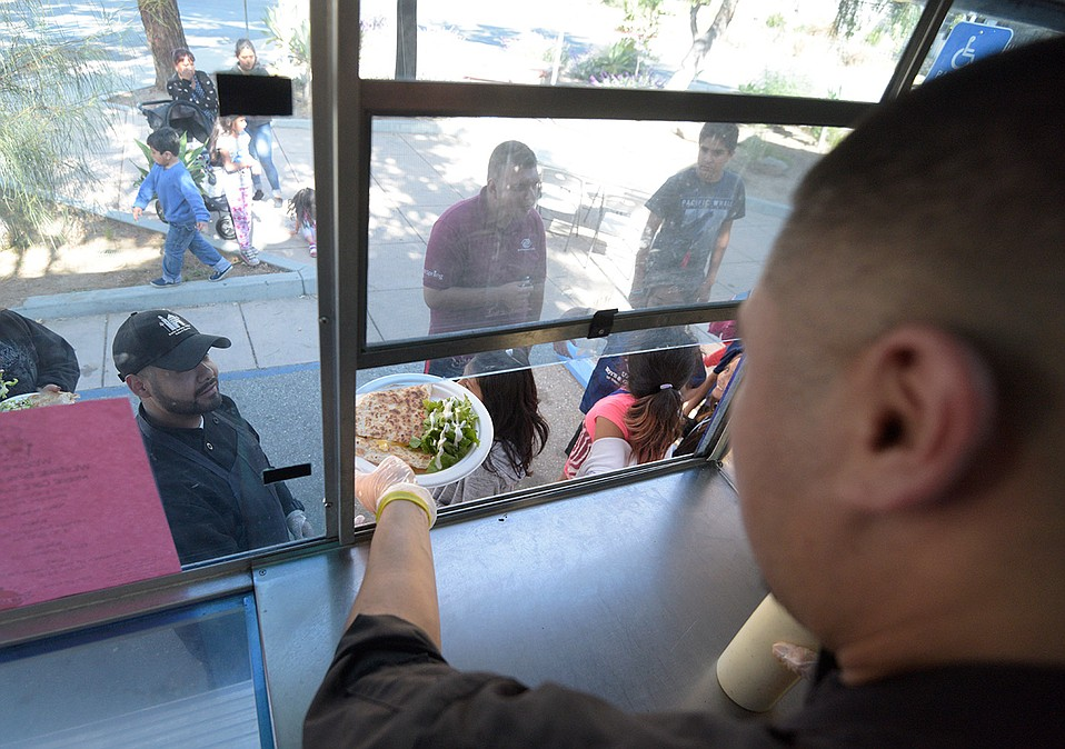 Lead food-truck cooks Juan Valladares and Juan Rojas (with cap) serve up quesadillas, salad, and fruit smoothies as part of the S.B. Unified School District's Mobile Café Project, which feeds more than 3,000 kids in the summer and will expand into Carpinteria and Buellton this June.