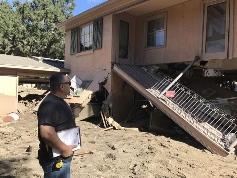 Rudy Raygoza inspects a red-tagged home near East Mountain Drive.