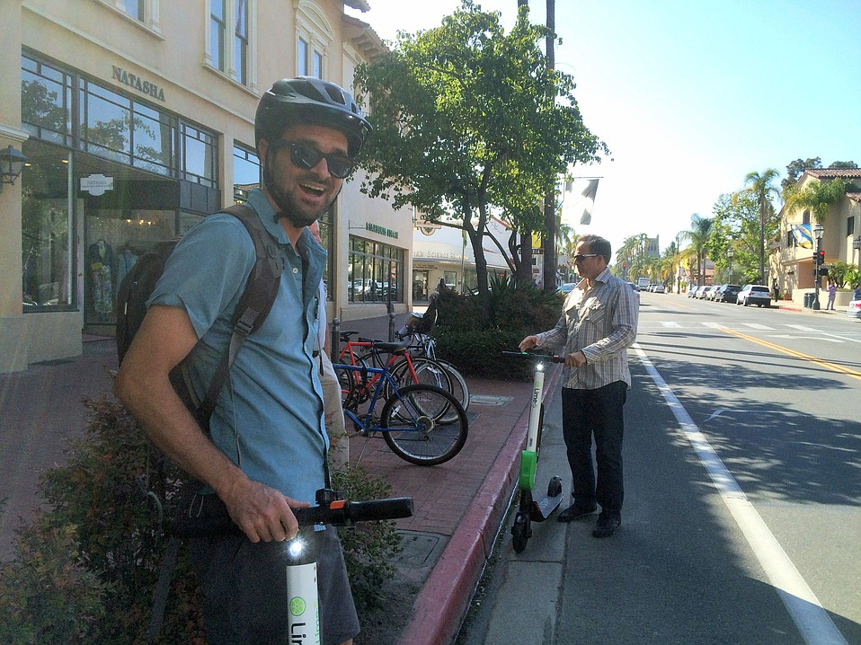 Santa Barbara Bicycle Coalition Executive Director Ed France (left) and City Councilmember Jason Dominguez try checkout Limebike scooters on State Street