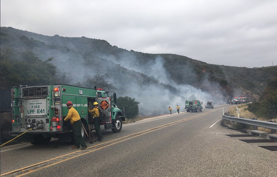 Los Padres National Forest and Santa Barbara County Fire Department crews extinguish several spot fires along highway 154 on Friday afternoon.