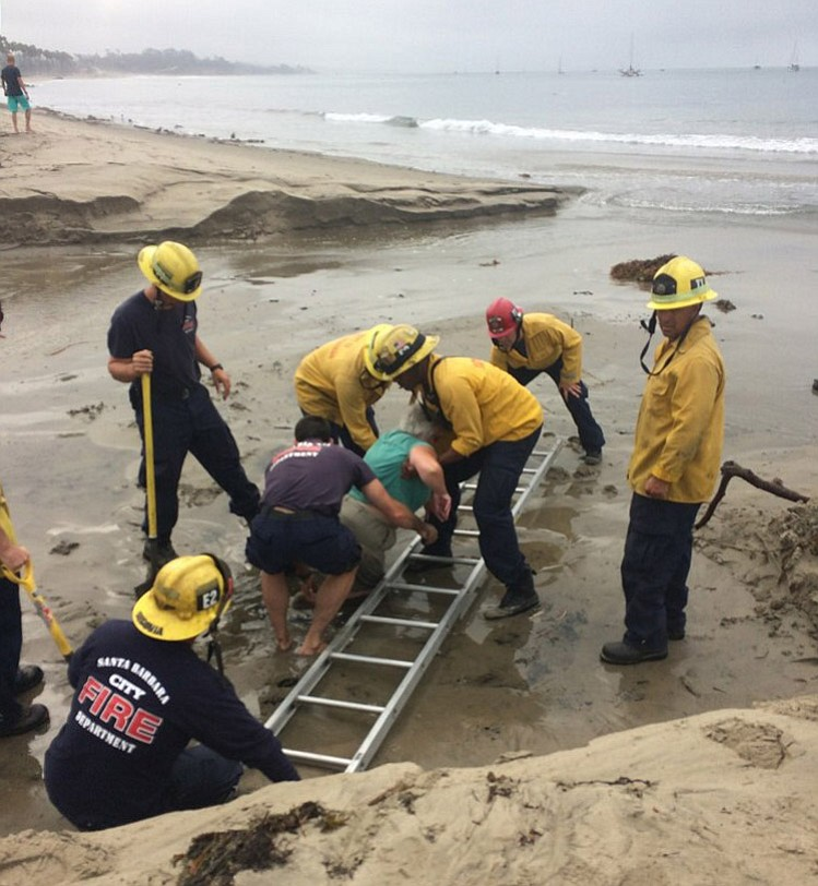 City firefighters rescue a woman found trapped in quicksand on East Beach.