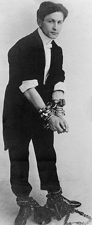 Harry Houdini, here pictured in chains circa 1905, was among the era's most vigorous opponents of the claims of psychic mediums.