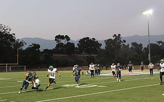 Dos Pueblos quarterback David Leon is tackled by a Pacifica defender.