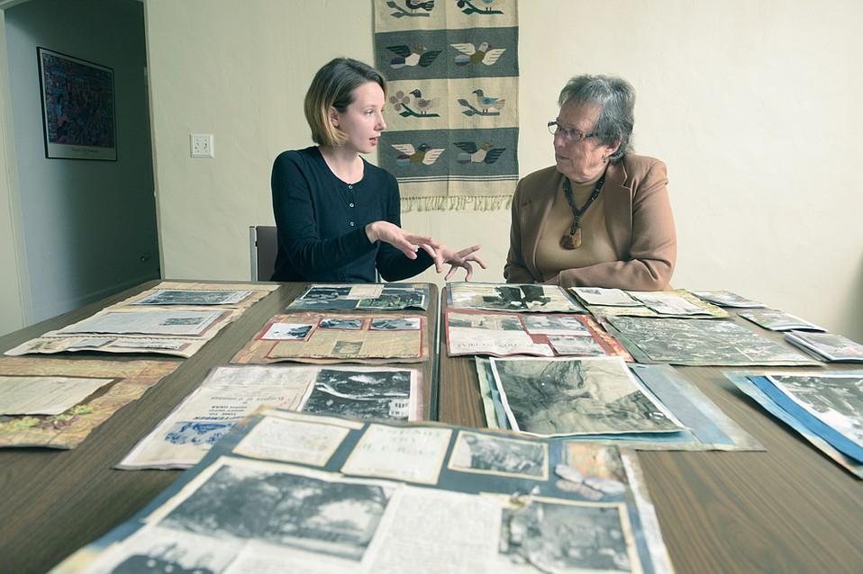 Conservator Christina Bean (left) and Stephanie Glatt, director emerita at La Casa de Maria, go over some of the photos salvaged following the 1/9 Debris Flow.