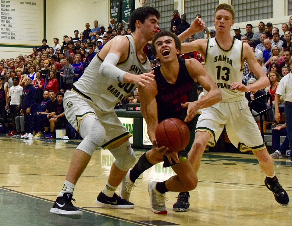 Santa Barbara High's Bryce Warrecker (left), with help from teammate Aiden Douglas (13), puts the clamps on San Marcos star Beau Allen.