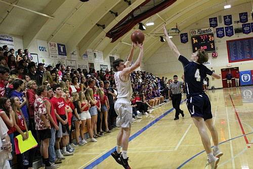 Tommy Condon releases a three-point shot over the outstretched arm of Jaron Rillie