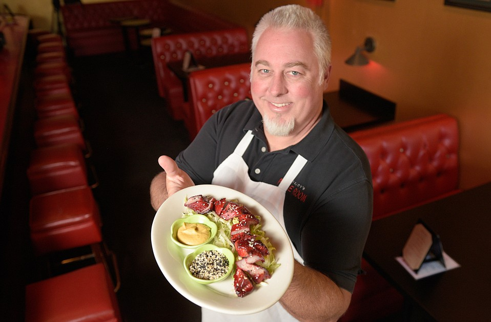 Three Pickles's owner Clay Lovejoy shows off a Jimmy's special Tommy's Famous Sliced BBQ Pork which is on the menu for a limited time during the start of the Chinese Year of the Pig.