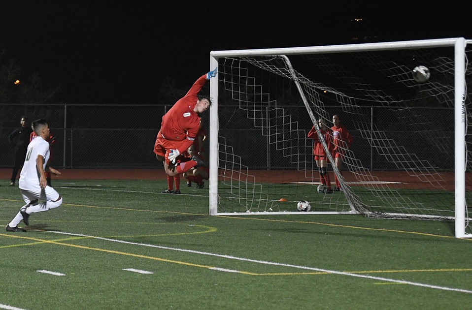 San Marcos goalkeeper Bryce Tomlinson can only leap and wave as a 19-yard free kick by Santa Barbara High's Juan Carlos Torres swerves into the net.