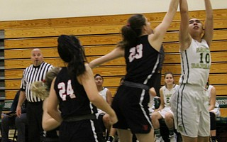Payton Johnson goes up for a shot over the oustretched arm of Amelia Schariff.