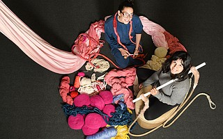 Artist Tamika Rivera (left) and S.B. Centre for Aerial Dance's Ninette Paloma sit in a pile of yarn below an aerial silk, both main ingredients in <em>Haven</em>.
