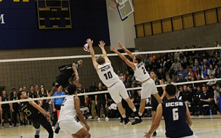 Louis Richard hits into the block of Casey McGarry and Brandon Hicks.